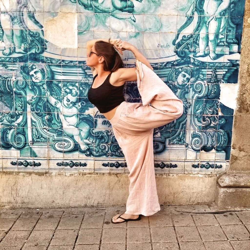 Woman doing yoga pose in front of blue tiled wall in Porto, Portugal.