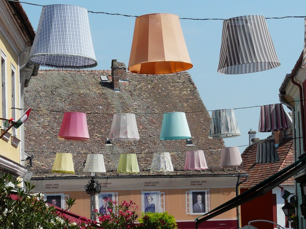 Pastel colored lampshades strung above a street in Szentendre, Hungary.
