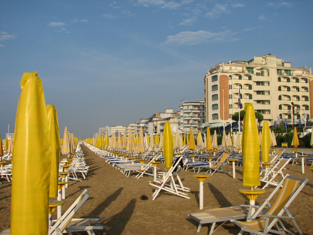Hundreds of empty yellow beach chairs and umbrellas before the crowds arrive at Lido di Jesolo