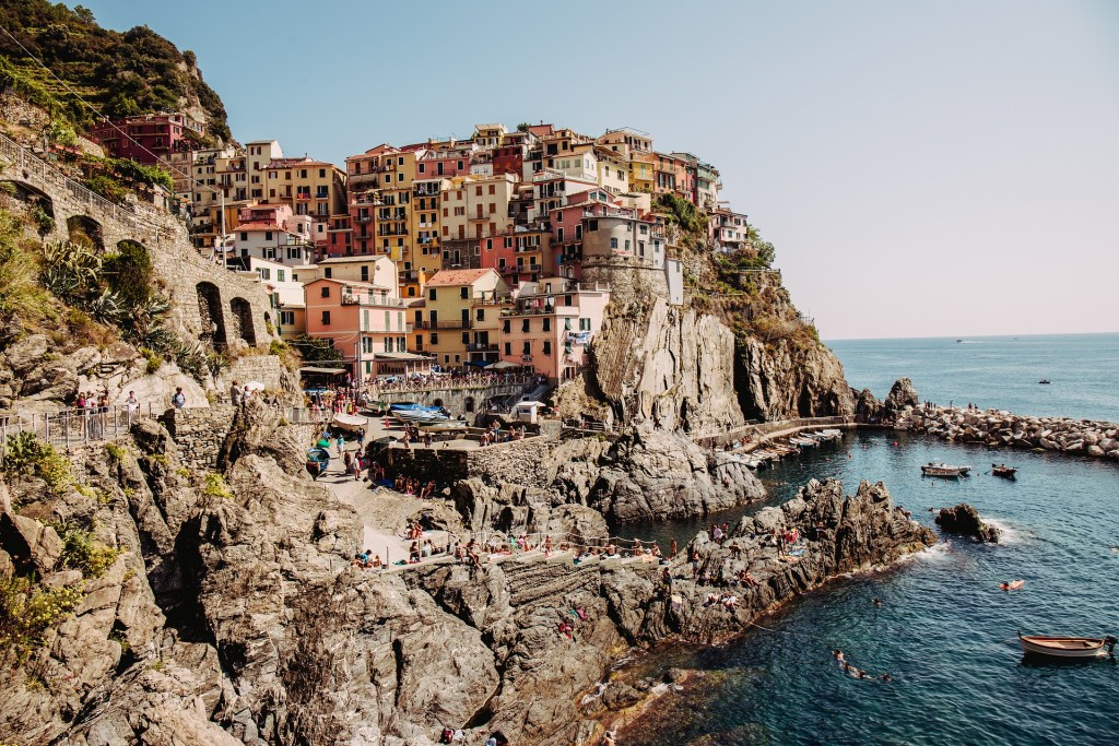 Manarola, Italy, in the Cinque Terre on the Mediterranean coast of Italy.  Pale turquoise waters crash on the peninsula with colorful buildings piled up on the cliffside in warm shades