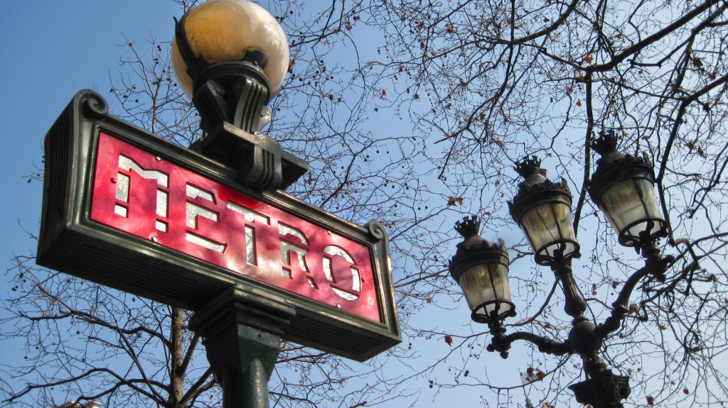 Red Paris metro sign shown with bare-branched trees and a lamp post in the background.