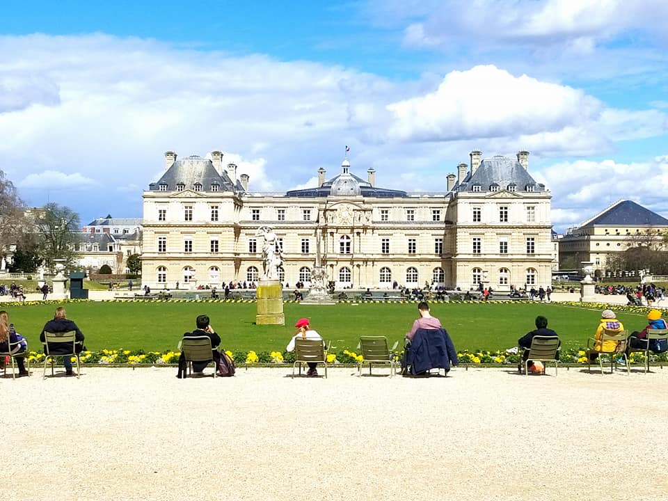 Parisians sitting in chairs around the Luxembourg gardens in Paris.
