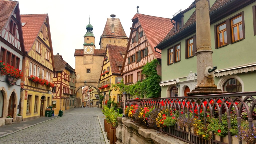 Colorful street of Rothenburg ob der Tauber with flowers planted in the windows and half timbered houses on the cobblestone street.