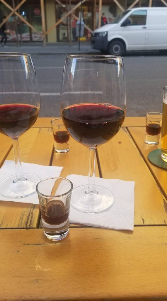 Three glasses of wine and three shots on a table at Sisters in Cluj-Napoca, Romania.