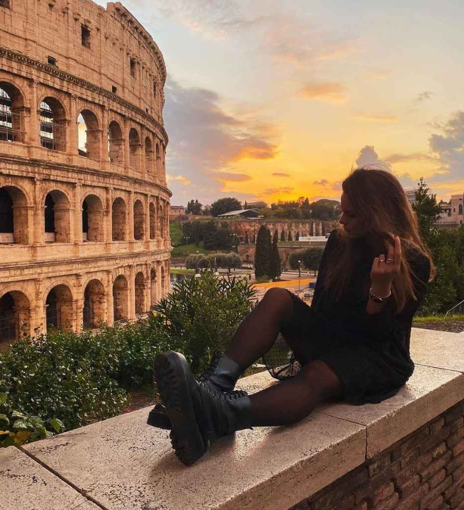Woman sitting on wall outside the Colosseum looking at it during sunset.