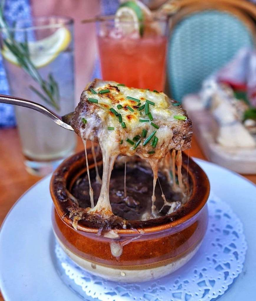 Spoonful of french onion soup above the crock it's been cooked in with cheese oozing down - one of the best French dishes to eat!