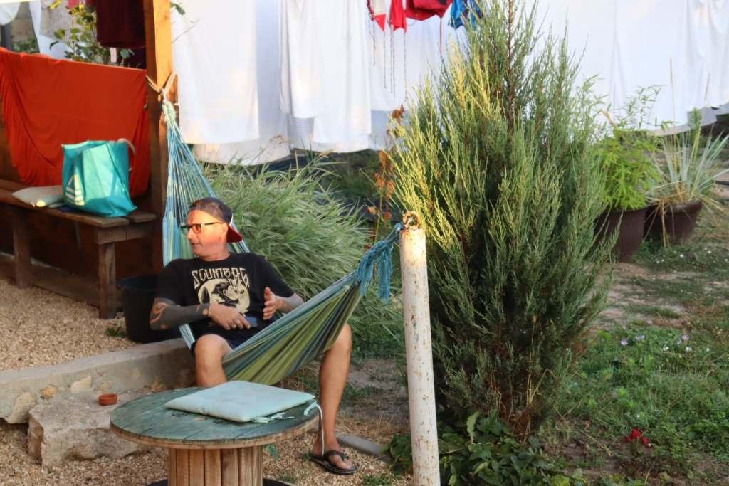 Man sitting on hammock at hostel in Vama Veche