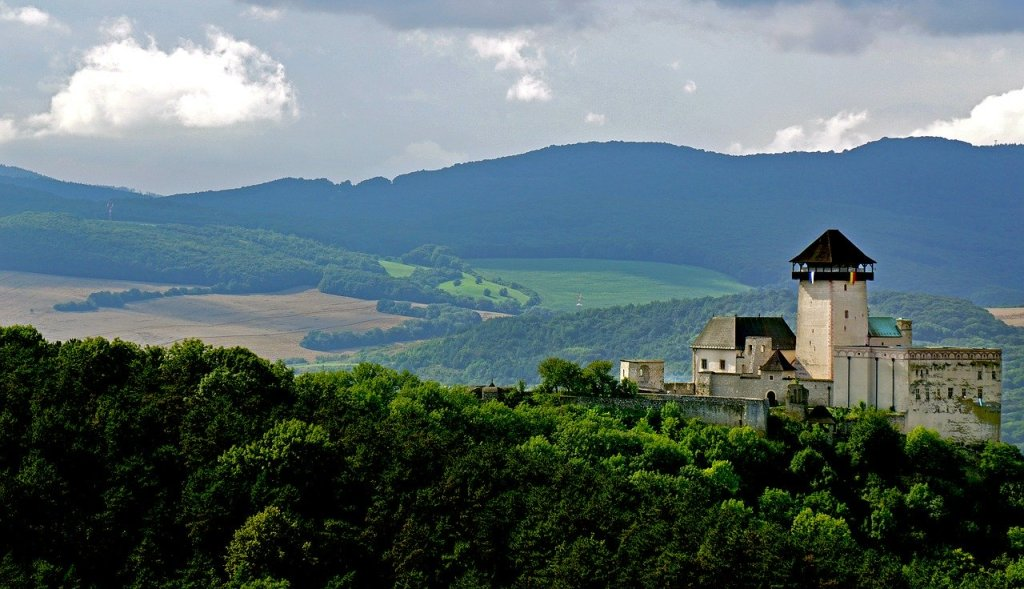 Trencin Castle from afar in the trees and mountains Slovakia bucket list