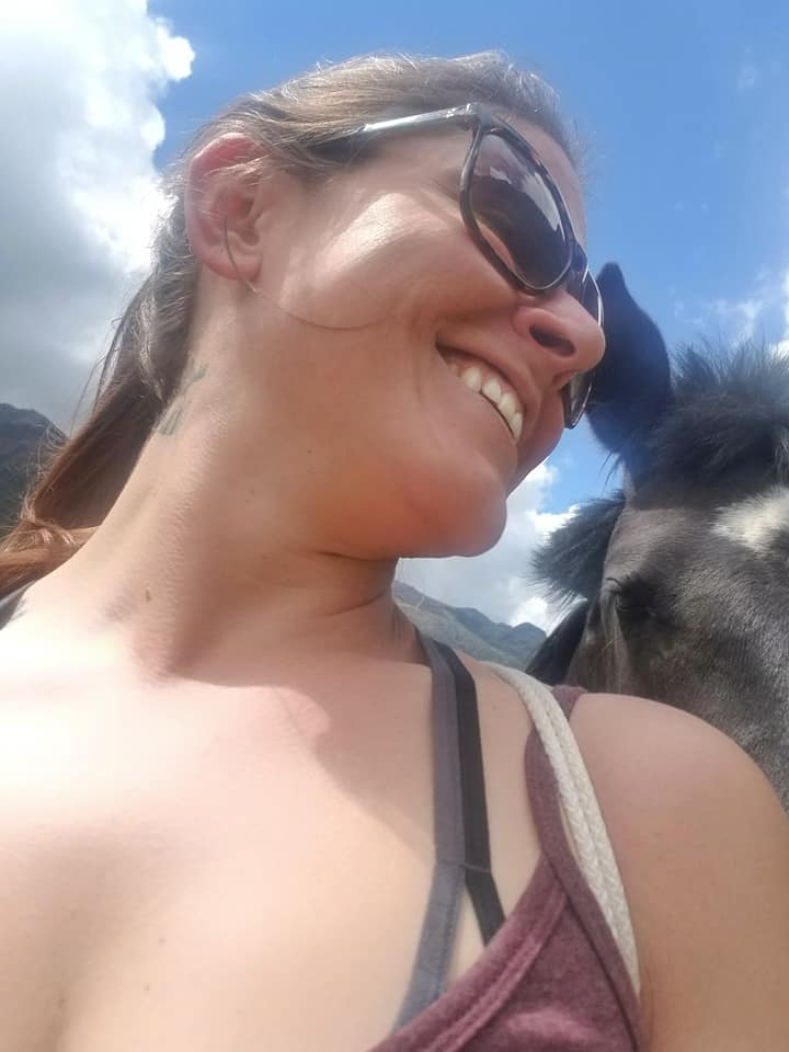 Woman taking selfie with wild horse from awkward angle