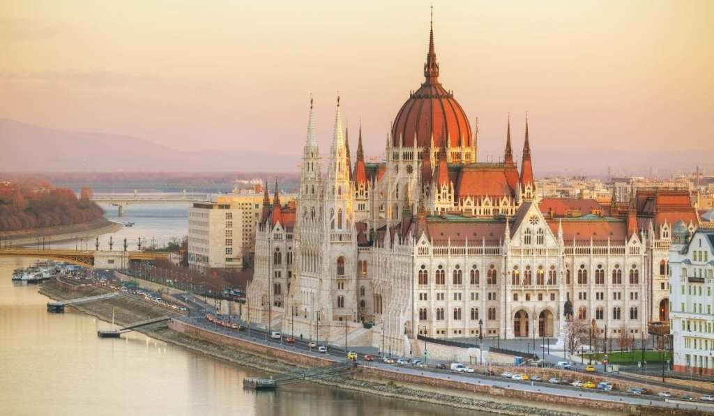 Budapest Parliament next to the Danube with pale pink and yellow sunset skies.