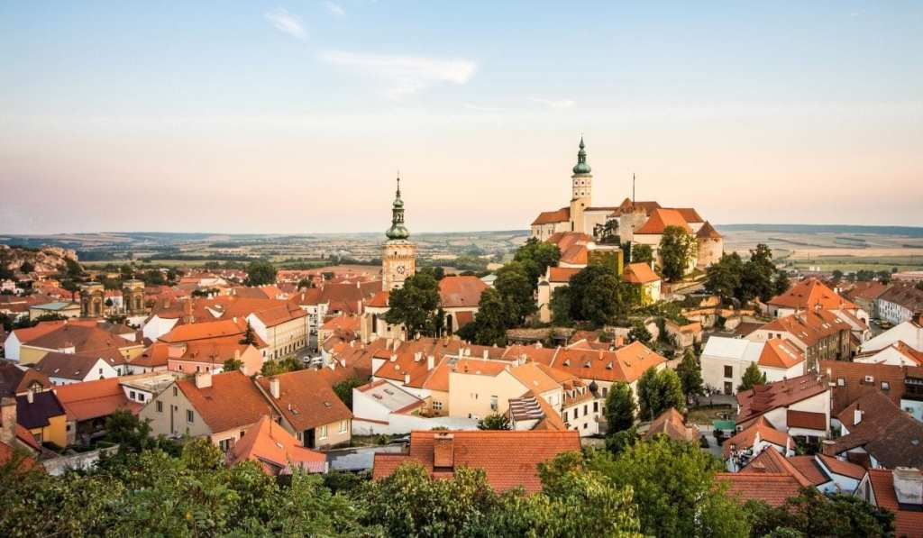 City skyline of Mikulov, Czech Republic at dusk with red roofs and green trees dominating the landscape.