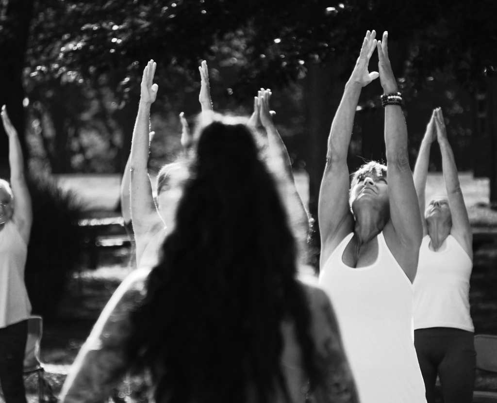 Group of people practicing yoga outside, black and white photo.  All students have arms up over their heads and are looking toward the sky.