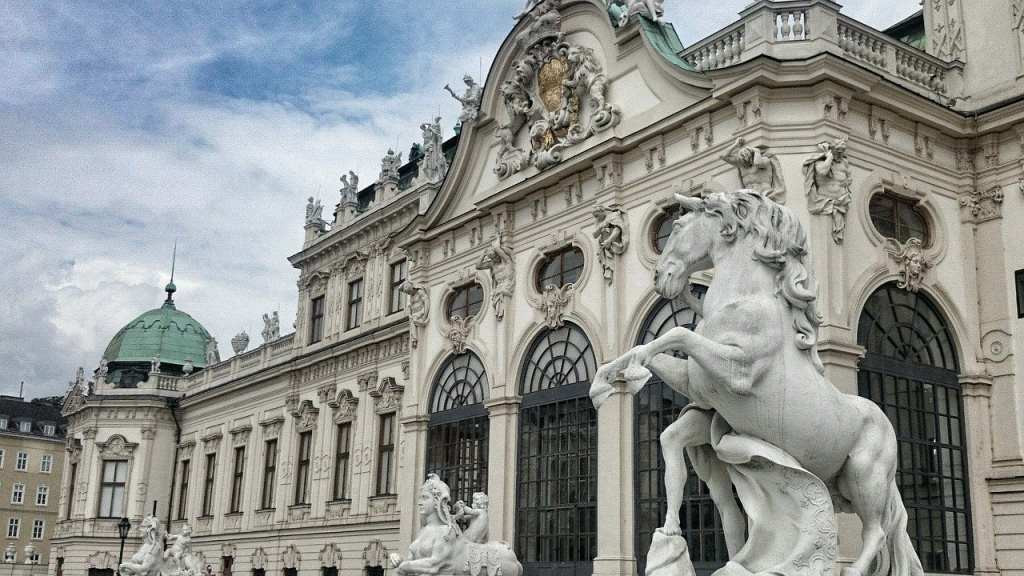 View of the Hofburg in Vienna with a horse statue in the foreground and the iconic seafoam green dome in the background.