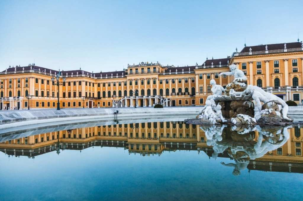 Schonbrunn Palace in Vienna with the building reflected in the fountain below.