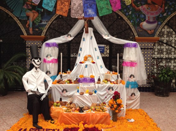 An altar built by Atlixco students, featuring lots of fruit, bread, and a mirror, and crowned by a crucifix.