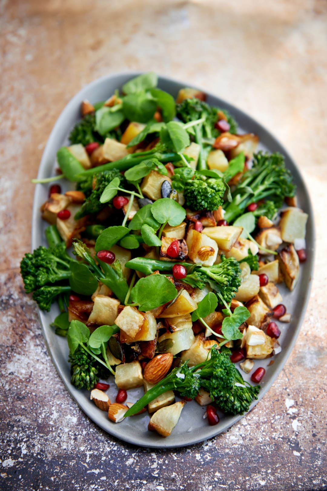 Freshly grilled vegetable salad with sweet potato, broccoli, almonds, pomegranate seeds, and spinach
