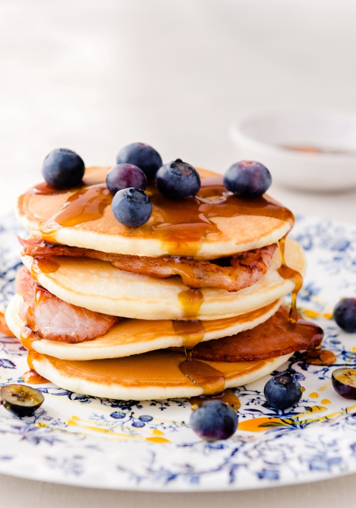 Delicious pancakes with bacon, blueberries and maple syrup flowing down the sides on vintage floral plate, delicious indulgent breakfast
