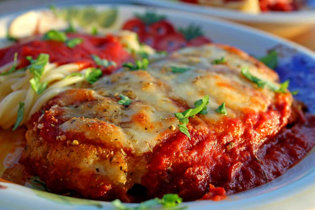 I practically drool just thinking about this delicious chicken parmesan. Lightly browned melted gooey cheese and fresh basil top these crispy breaded chicken breasts lying on a bed of tomato sauce with a side order of spaghetti. This is food that comforts the soul!