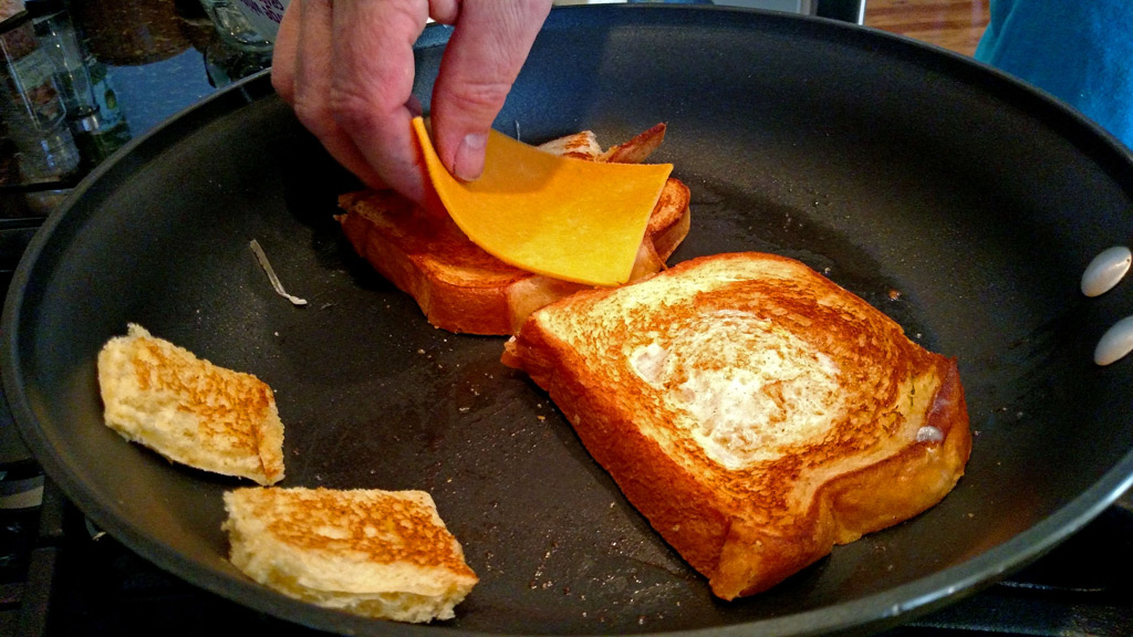 Eggs in a basket is a quick and easy breakfast, these eggs are fried inside a hole cut into a slice of bread and topped with melted cheese. | TheMountainKitchen.com