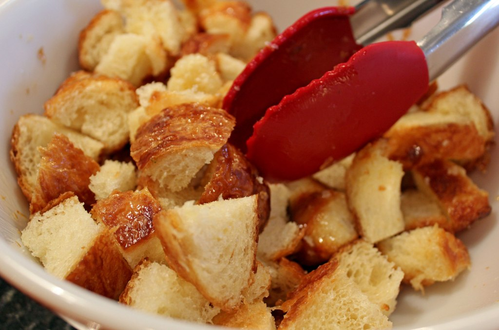 bread cubes in a bowl with tongs