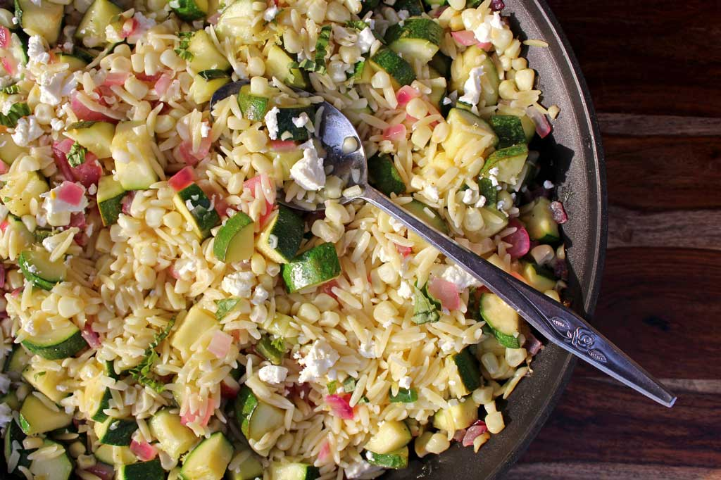 Summer is bursting with flavor in this corn zucchini orzo salad. Seasonal vegetables combined with lemony orzo and feta cheese for a quick pasta salad. Yum! | TheMountainKitchen.com
