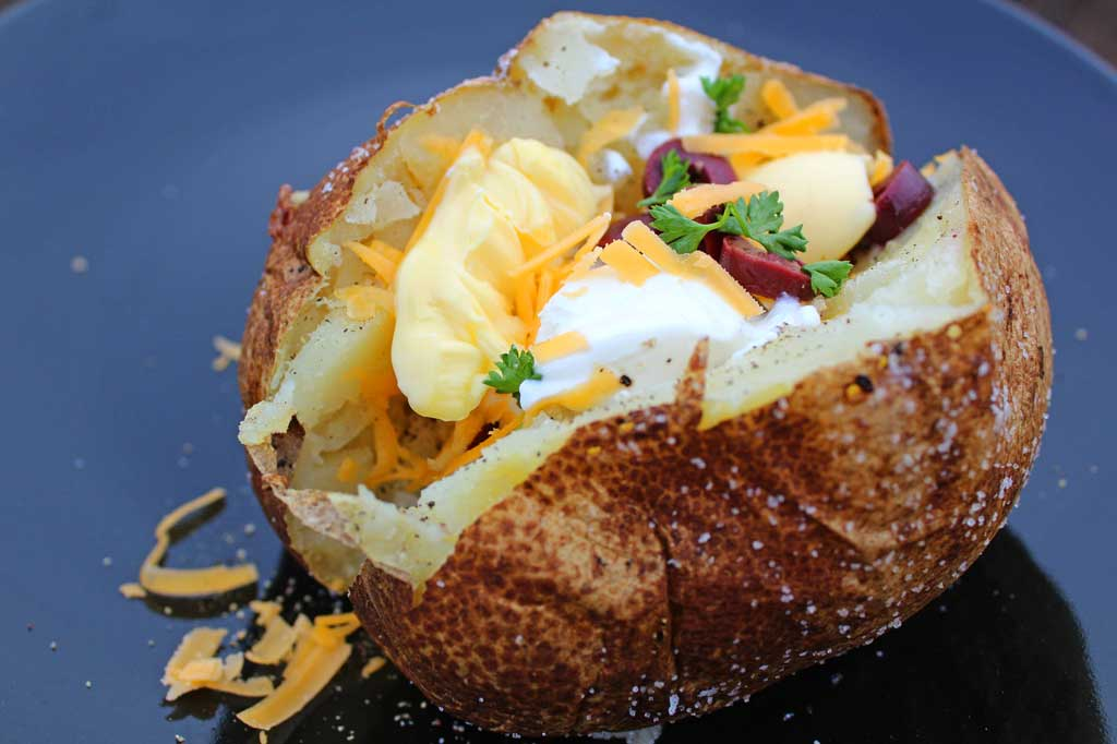 Steakhouse baked potatoes have a salted crispy, golden skin with a light with a warm fluffy center. Learn how to make these perfect baked potatoes at home! | TheMountainKitchen.com