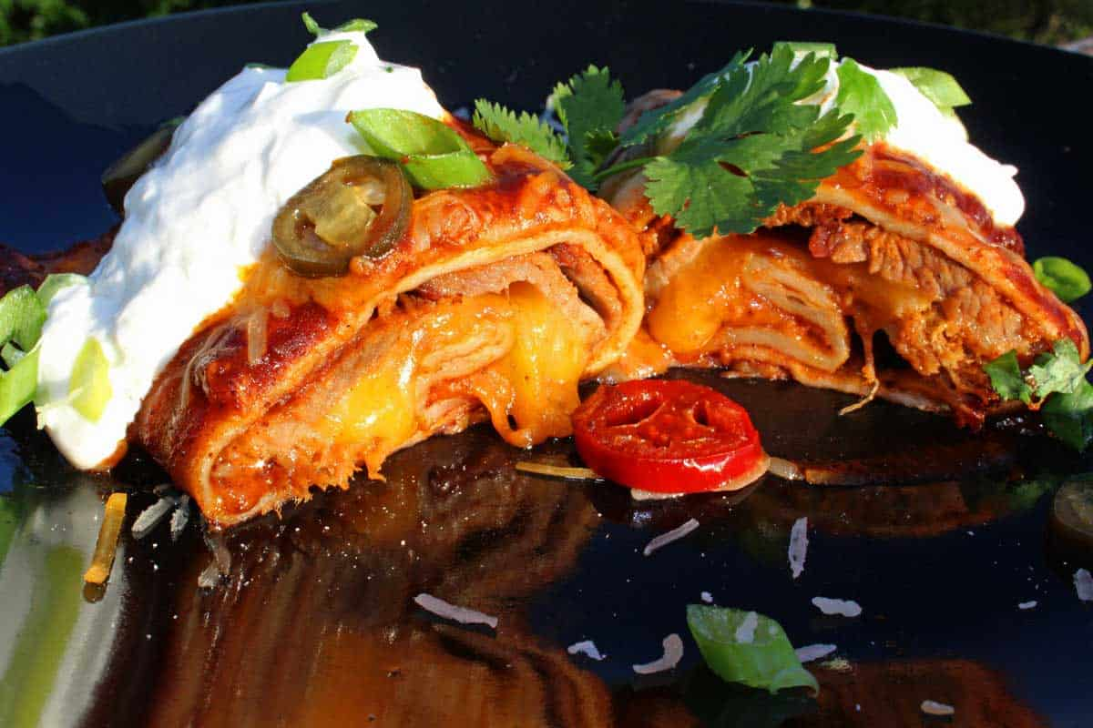 Leftover brisket? Make this recipe for smoked beef brisket enchiladas! Smoky brisket wrapped in tortillas smothered in enchilada sauce and gooey cheese.