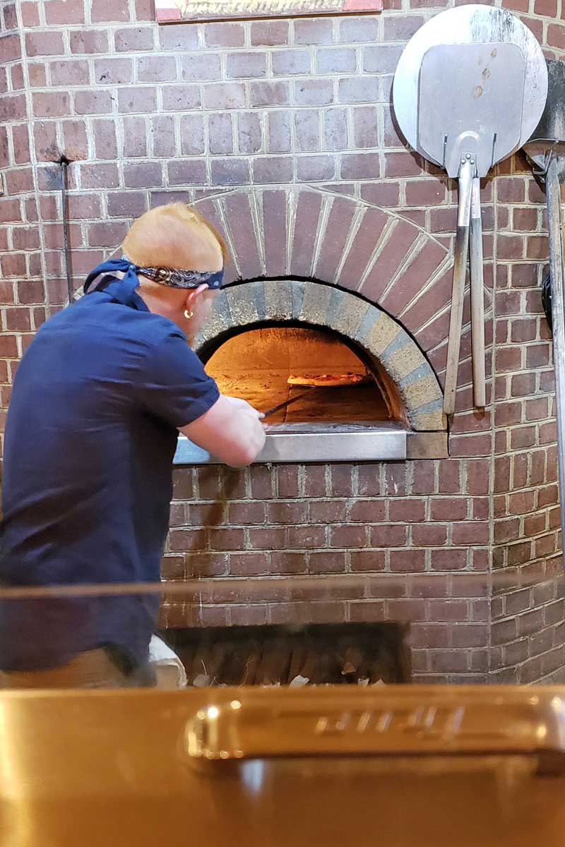 guy tending to pizza oven