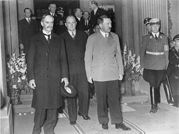 Unsmiling, Chamberlain (left) and Hitler leave...