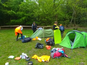 scouts breaking camp, with kit in front of their tents