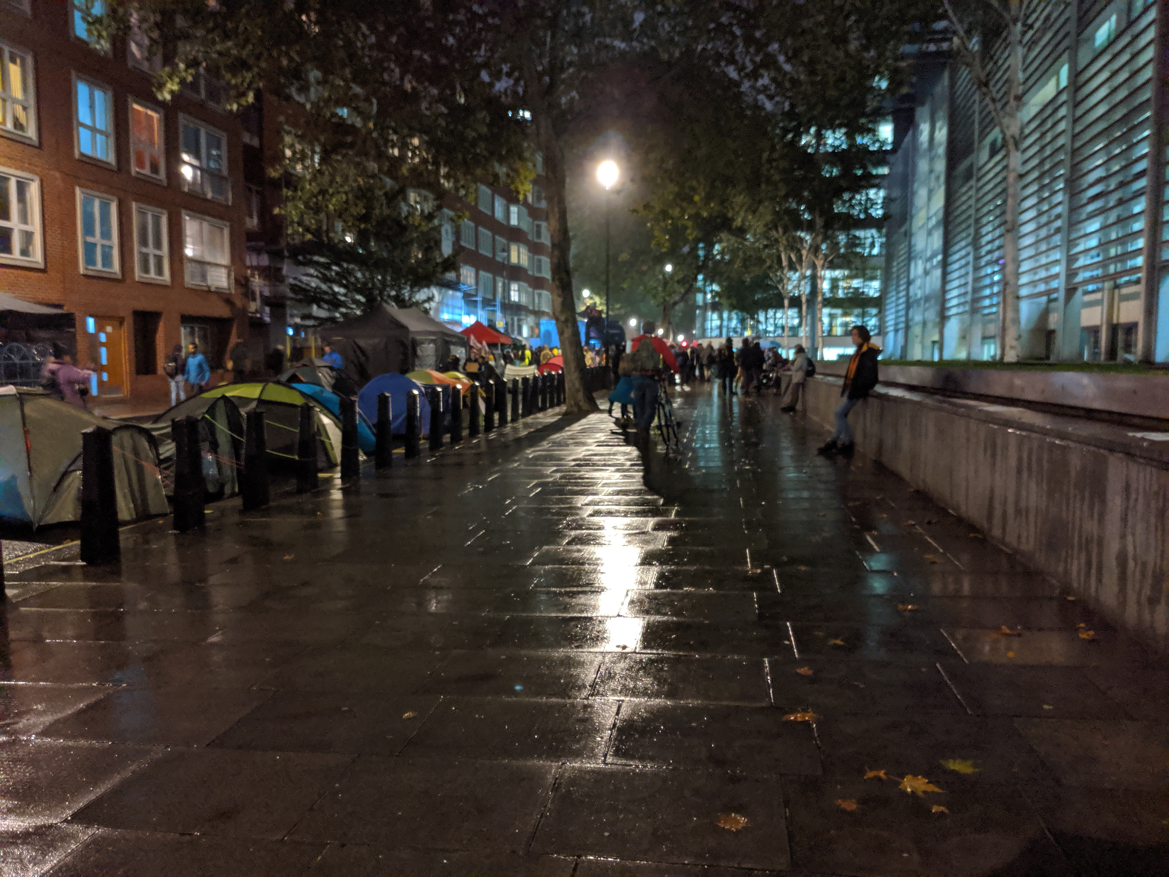 Extinction Rebellion settling in for the night. Streetlight reflected off the rainy pavement with tents set up along Marsham Street. Entertainment in front of the main entrance to the Home Office building. (photo: James Kemp)