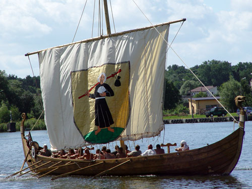 A replica Viking Longship, with raised sail and rowers. The sail has an image of a man travelling with his belongings in a bag in a staff over his shoulder.