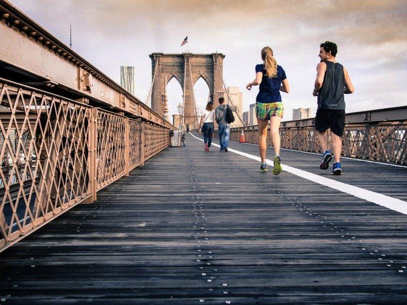 Two friends running side by side on a bridge Take a friend - ways to enjoy running