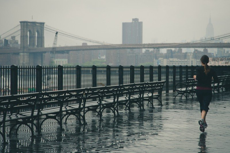 woman running in the rain next to benches and bridge in background Beginner Runner Frequently asked questions