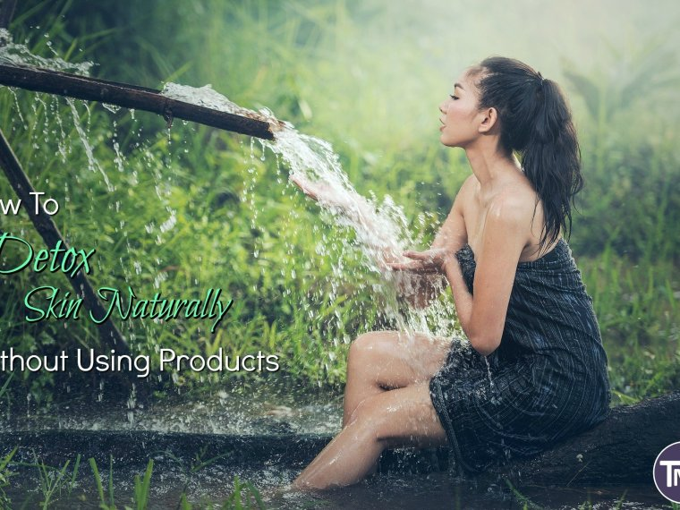 woman under a natural wooden hose fountain with grass background washing forearms