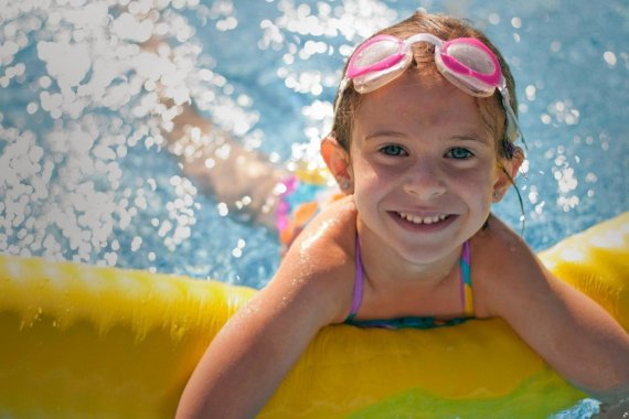 girl smiling in swimming pool - justifying using the benefits of swimming