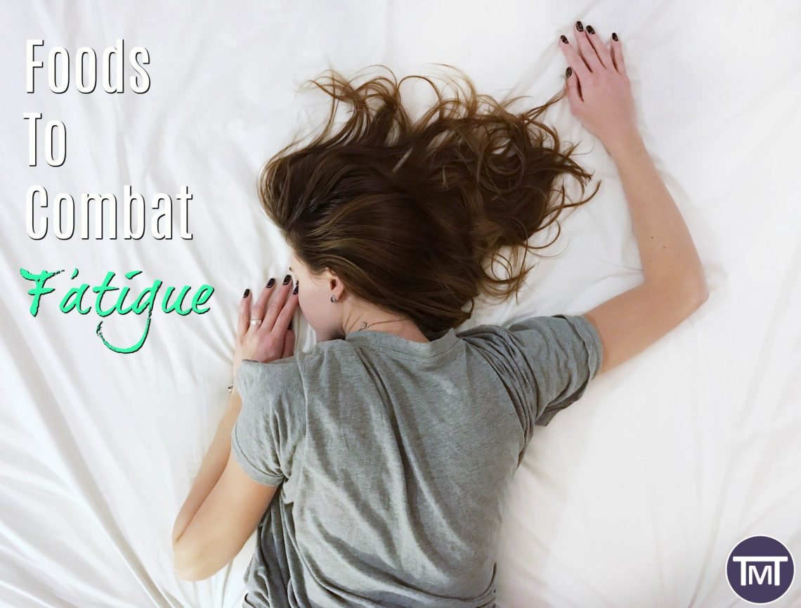woman lying face down on bed with grey t-shirt with text overlay - foods to combat fatigue feature image