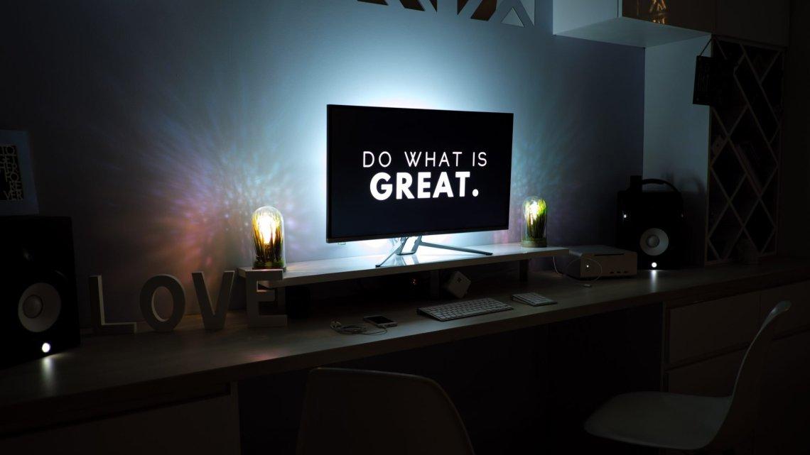 "tv illuminated in darkened living room saying ""do something great."""