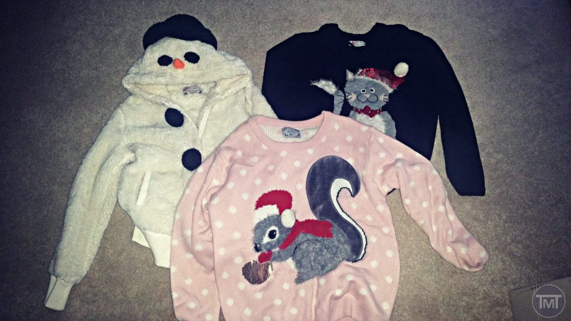 my three ugly Christmas sweater on the floor, one white snowman jumper, one pink squirrel in a santa hat and a black Cat in a Christmas hat.
