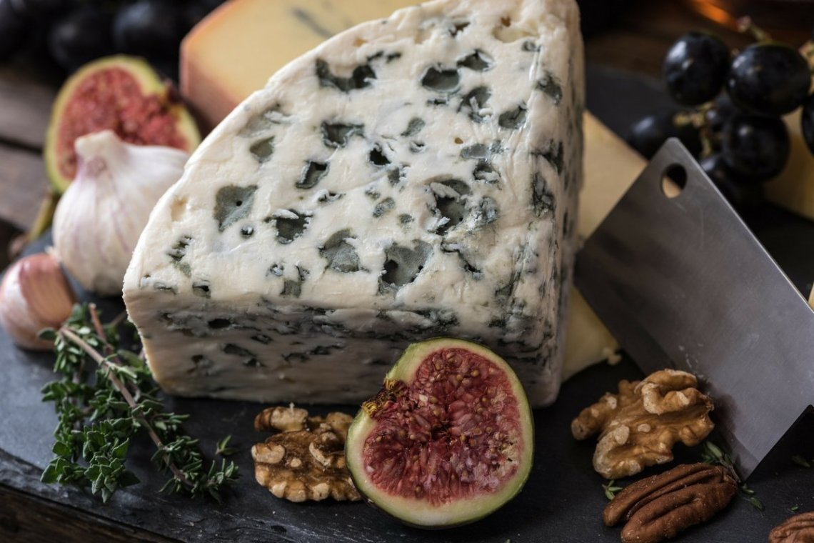 giant triangle of blue cheese surrounded by figs