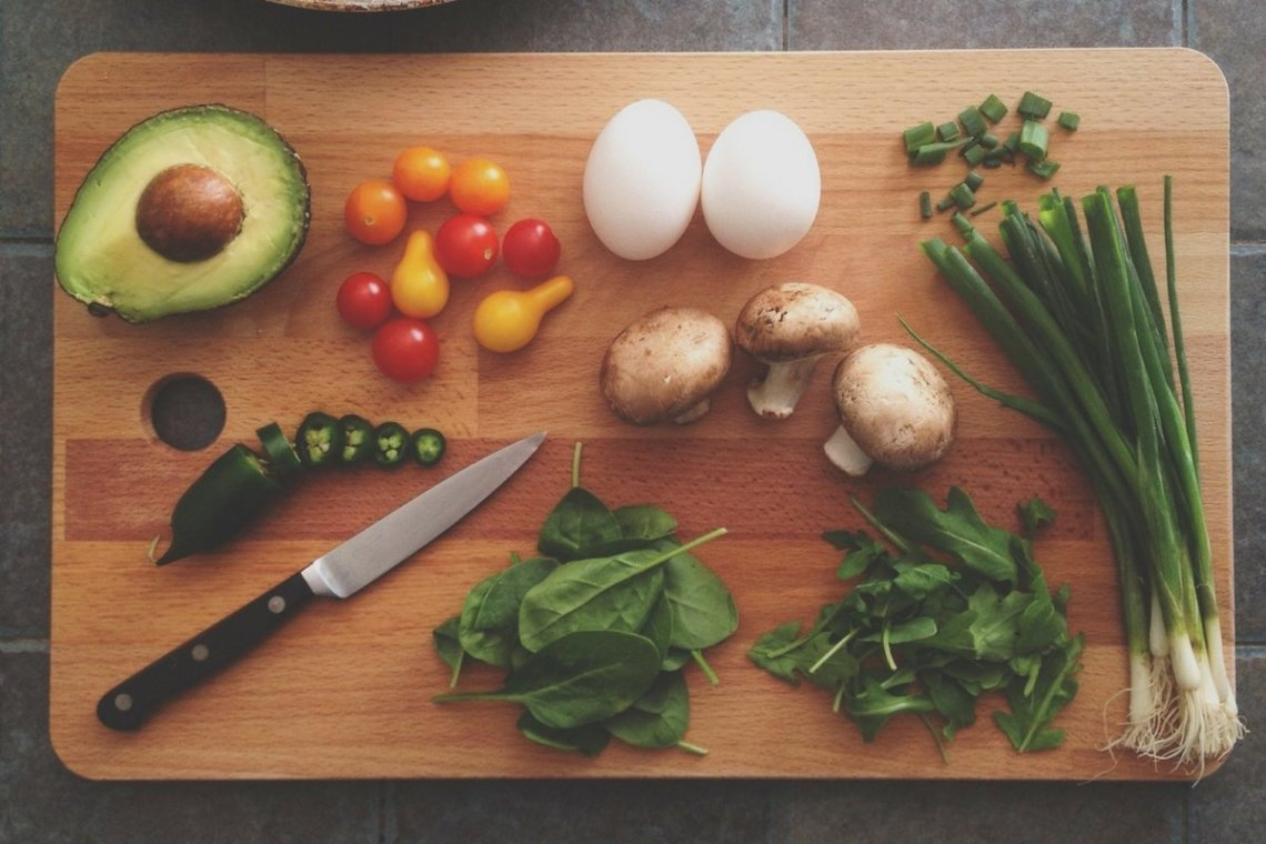 board of raw veggies with eggs and avocado