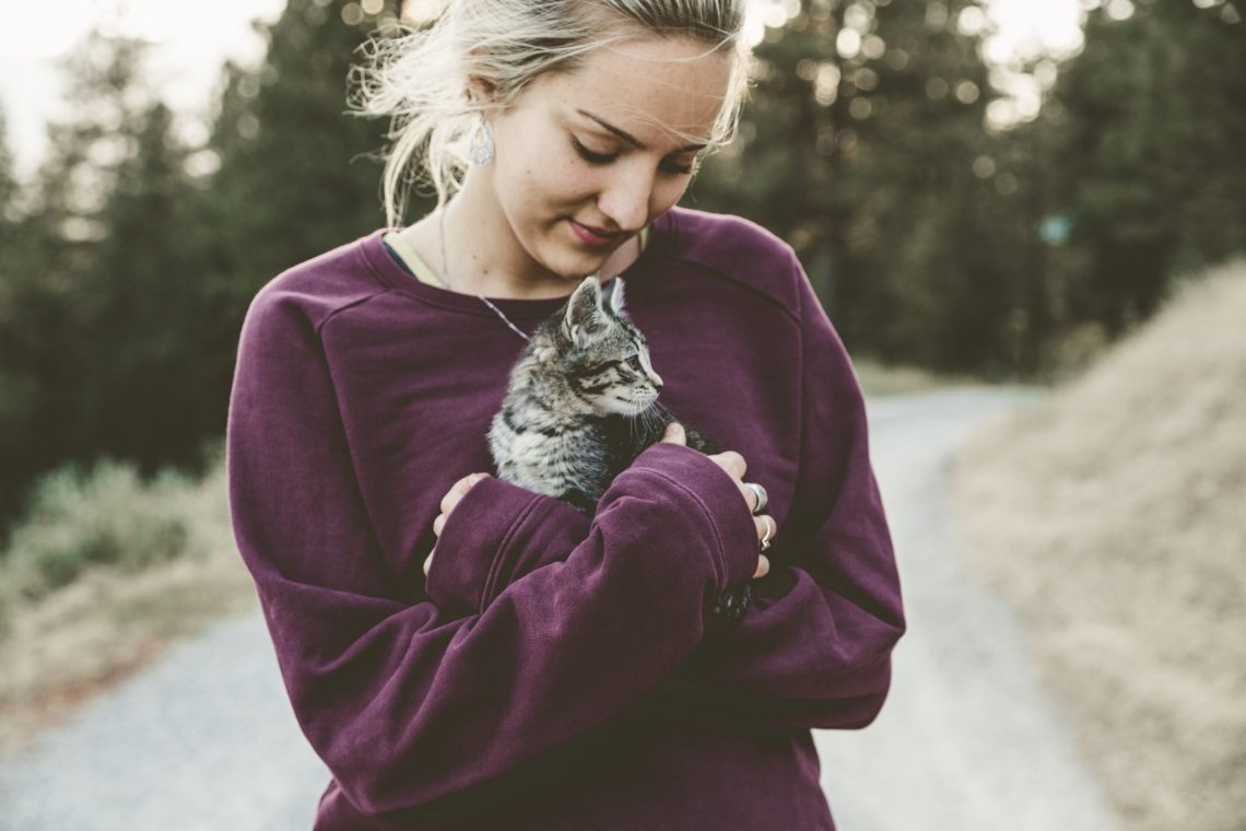 woman in purple jumper cuddling tabby kitten on a road with trees in the background