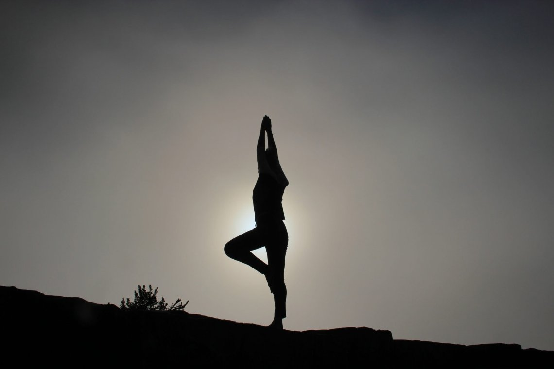 silhouette of a lady doing yoga
