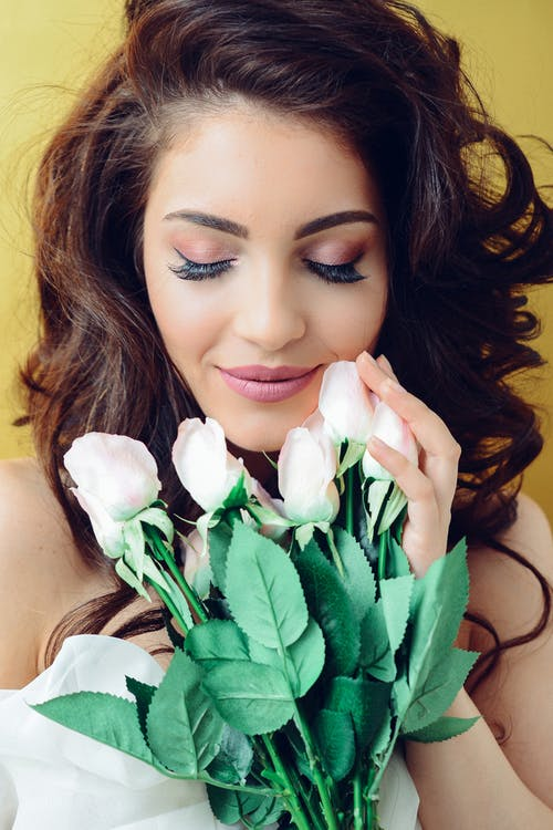 Brunette holding white roses up to her face with her eyes closed and long, fake lashes