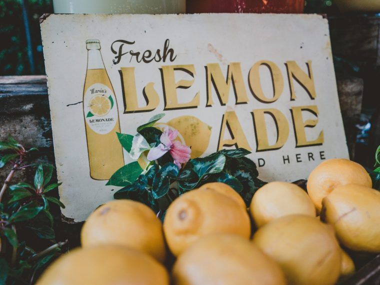 lemonade stand with lemons in front of it. Feature image for lemonade recipes