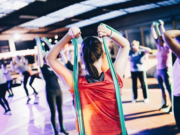 fitness class with woman stretching with rubber bands and avoiding skipping the gym