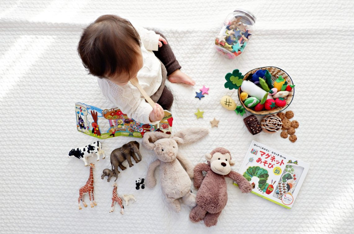 baby on a white rug playing with toys