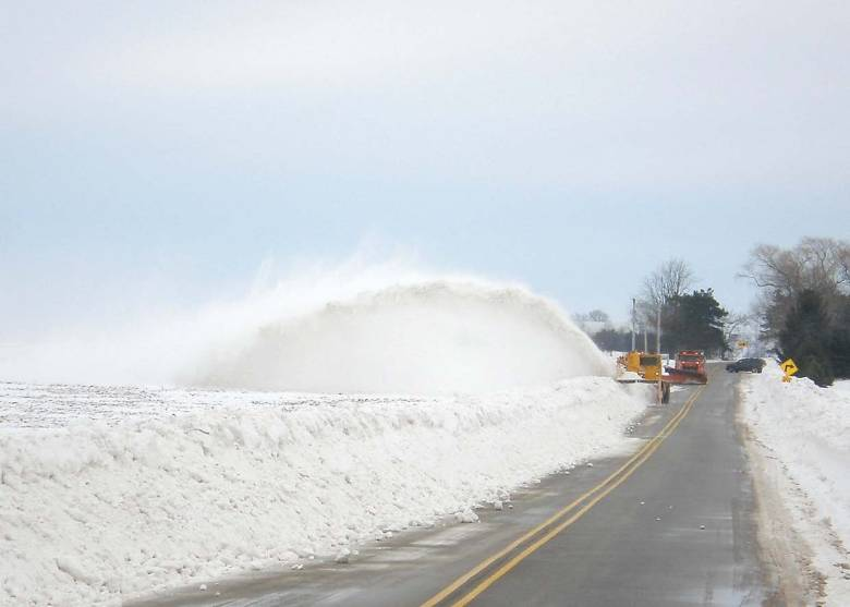 A snowblower and county truck work together to remove large drifts following a blizzard in January 2014. (Provided by APWA Winter Maintenance Technical Committee)