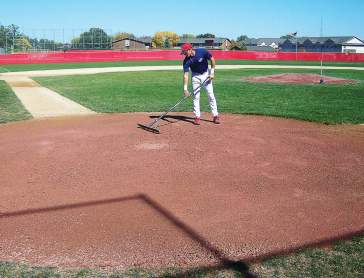 A ballplayer spreads Flex-A-Clay in the area of the batter's box and home plate. (Photo provided)