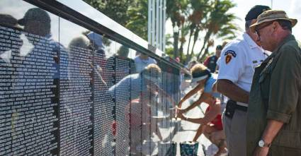 Moments after the Southwest Florida Vietnam Memorial Wall dedication people walk along it, some seeking names. (Photo provided by Punta Gorda)
